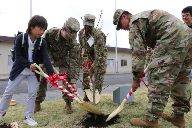 Rento Sakurai, a third-grader at LCA Kokusai Elementary School, plants a cherry blossom tree with Soldiers assigned to the 38th Air Defense Artillery Brigade as symbol of friendship during an Earth Day event April 24 at Sagami General Depot, Japan. (U.S Army photo by Noriko Kudo)