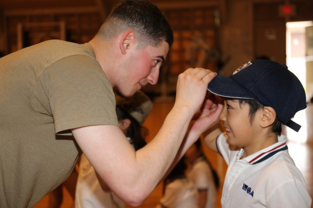 Pvt. James Moore, assigned to the 38th Air Defense Artillery Brigade, shows an LCA Kokusai Elementary School student how to salute during an Earth Day event April 24 at Sagami General Depot, Japan. (U.S Army photo by Noriko Kudo)
