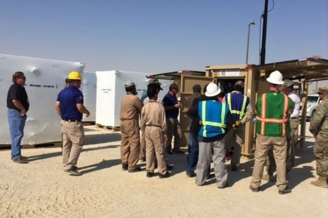 Representatives from the Camp Arifjan, Kuwait, Director of Public Works, Idaho National Labs and their expeditionary resource efficiency managers participate in a demonstration of the solar light cart with hydration unit option at Camp Arifjan, Kuwait, Oct. 3, 2018. The demonstration allowed for the DPW and their operations and maintenance personnel to be aware of how to properly set up the units and how to operate and maintain the units to ensure maximum efficiencies. (U.S. Army photo courtesy of Karen R. Moore)