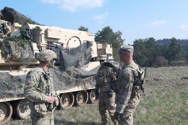 U.S. Army Capt. Jay Beeman, advisor team leader, Bravo Company, 5th Battalion, right, and Staff Sgt. Paul Clever, engineer advisor, center, discuss Armored Breach Vehicle employment with Cpl. Perry, Company A, 1st Engineer Battalion, 1st Armored Brigade Combat Team, 1st Infantry Division, during simulated offensive operations in Allied Spirit X, an exercise which included approximately 5,630 participants from 15 nations at the 7th Army Training Command's Hohenfels Training Area from March 30 to April 17, 2019.