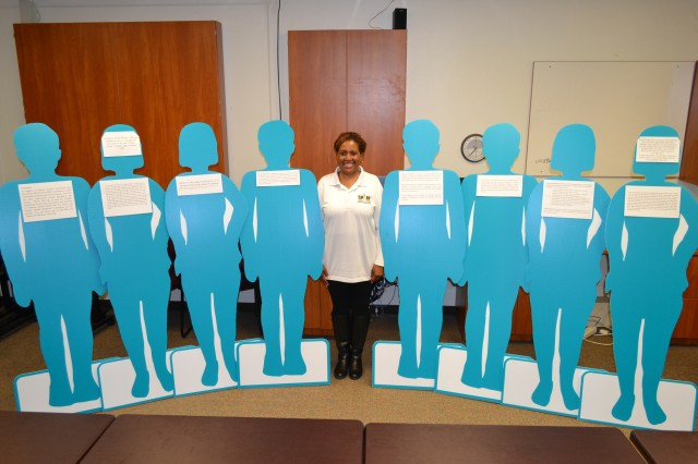 Ms. Tia Moore, Sexual Assault Response Coordinator, Keller Army Community Hospital, poses with her team of 'teal-colored silhouettes' provided SAAPM messages throughout the hospital. The silhouettes provided sexual assault awareness messages and statistics to Keller staff and hospital visitors.