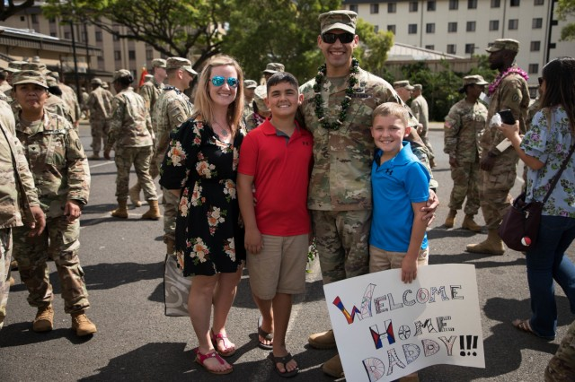 Family members hold up signs welcoming home Soldiers from the 524th Combat Sustainment Support Battalion during redeployment ceremony April 30, 2019 at Schofield Barracks, Hawaii celebrating the successful completion of a 9-month combat tour in support of Operations Spartan Shield, Inherent Resolve, and Freedoms Sentinel. (U.S. Army Photo by Sgt. Sarah D Williams)