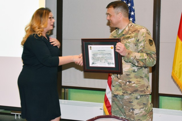 U.S. Army Garrison Wiesbaden Commander Col. Noah Cloud presents the award for Adult Family Member Volunteer of the Year to Amber Koeckritz April 26 at the Volunteer Recognition Ceremony at the Community Activity Center on Clay Kaserne. Overall, volunteers donated more than 87,000 hours of their time to the garrison over the past year.