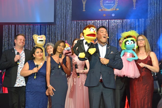 """The cast of """"Avenue Q,"""" from U.S. Army Garrison Wiesbaden's Amelia Earhart Playhouse perform """"For Now"""" at the 2019 Toppers April 27 at the USAG Wiesbaden fitness center. Toppers celebrates the best in theater across military communities in Europe."""