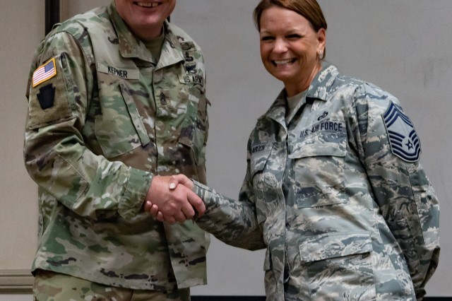 Command Sgt. Maj. Christopher Kepner, Senior Enlisted Advisor to the Chief of the National Guard Bureau, gives a coin to Chief Master Sgt. Jenny Balabuch, the Air Staff Superintendent at Joint Forces Headquarters, at the Michigan National Guard Joint Junior Leadership Conference held April 24-26, 2019, at Alpena Combat Readiness Training Center. This is the first time both Michigan Air and Army National Guardsmen, ranks E1-E6, have joined to attend a professional development event like this.