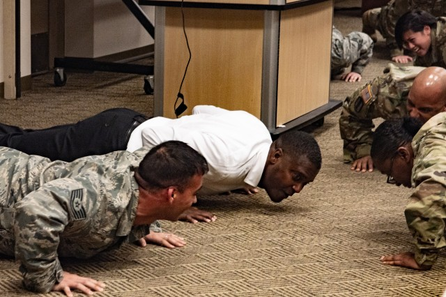 Orvie Baker, a former member of the 82nd Airborne Division, leads Michigan National Guard Airmen and Soldiers in push-ups at the Michigan National Guard Joint Junior Leadership Conference held April 24-26, 2019, at Alpena Combat Readiness Training Center. This is the first time both Michigan Air and Army National Guardsmen, ranks E1-E6, have joined to attend a professional development event like this.