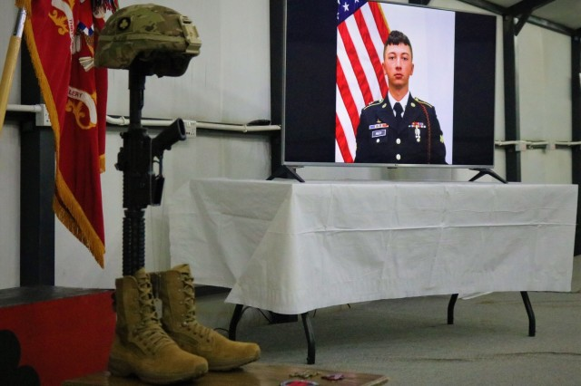 Identification tags for Spc. Ryan Riley hang from the Fallen Soldier Cross during a unit memorial service in Qayyarah West Airfield, Iraq, April 25, 2019. The Fallen Soldier Cross, also known as a Battle Cross, dates back to at least the American Civil War as a means of identifying the location of fallen Soldiers on the field. Today it is often a means of showing respect for the dead among the living members of the unit. (U.S. Army National Guard photo by Sgt. Roger Jackson)