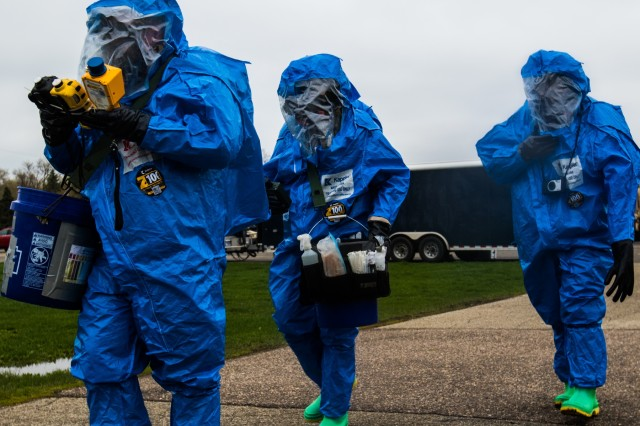 Michigan National Guard Soldiers assigned to the 51st Civil Support Team, wearing HAZMAT suits, investigate the scene of a simulated chemical attack at Kalamazoo County Fairgrounds April 30, 2019, as part of Northern Exposure 2019. NE 19 is a simulated nuclear detonation exercise which will provide realistic training to prepare MING units to integrate with civilian partners and respond to natural or man-made catastrophic events.