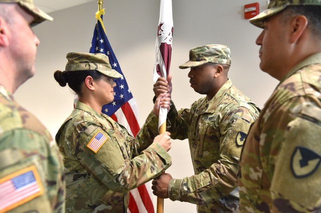 Incoming U.S. Army Medical Materiel Agency Detachment Commander Capt. Ivette Daley (middle left) passes the unit colors to Sgt. 1st Class Lamont Mitchell (middle right) during a change of command ceremony April 30 at Fort Detrick, Maryland. Daley assumes command from outgoing detachment commander Capt. Felipe Rodriguez (far right). USAMMA Commander Col. Timothy Walsh (far left) serves as the presiding officer over the ceremony.