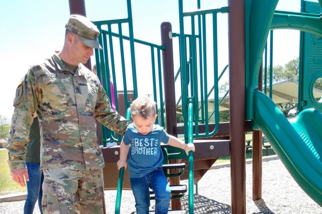 Sgt. 1st Class Ricky Hill, 504th Expeditionary Military Intelligence Brigade, helps his son on the playground, April 26, 2019, Fort Hood, Texas. The Hills started the adoption process one-and-a-half years prior to adoption.