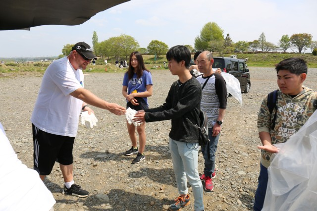 James Brown, chief of the U.S. Army Garrison Japan's Directorate of Public Works' Environmental Division, hands out gloves to volunteers to use during an Earth Day clean-up event in Zama City on April 21, 2019.