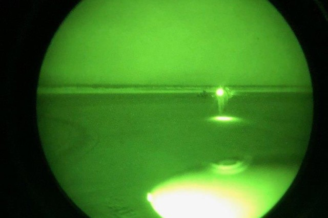 Seen through night vision goggles, Alaska Army National Guard UH-60 Black Hawk crew chief, Spc. Jeff Hartmann approaches a hunting party gathered by their campfire on a small island sandbar on the Yukon River in Alaska, May 1, 2019. Two of the hunters broke through the ice at about 2 a.m. while traveling over the river on snowmachines, and lost their transportation and all of their gear. They were stranded, wet and cold as they awaited rescue. Soldiers with the Alaska Army National Guard's 207th Aviation transported the two hunters via Black Hawk helicopter to Mountain Village, a coastal community in western Alaska that sits along the Yukon River. Alaska State Troopers contacted the Alaska Rescue Coordination Center to request a search and rescue mission out of Bethel, where an Alaska Army National Guard UH-60 Black Hawk and aircrew are stationed full-time.