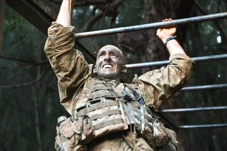 A Soldier scales the monkey bars as part of the Green Mile physical endurance course during week three of the Jungle Operations Training Course at the Lightning Academy, Wahiawa, Hawaii, April 18, 2019. JOTC spans over three weeks where Soldiers learn to communicate, navigate, and maneuver in any tropical jungle environment.