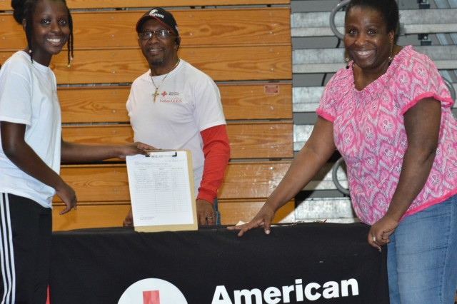Leah Pierre, left, 17-year-old youth Volunteer of the Year and American Red Cross VolunTEEN president, signs up new volunteers during Family Fun Day April 26 with her step father, Thomas Draper, and her mom, the group's parent lead/youth chair, Sharon Brown-DraperPierre.