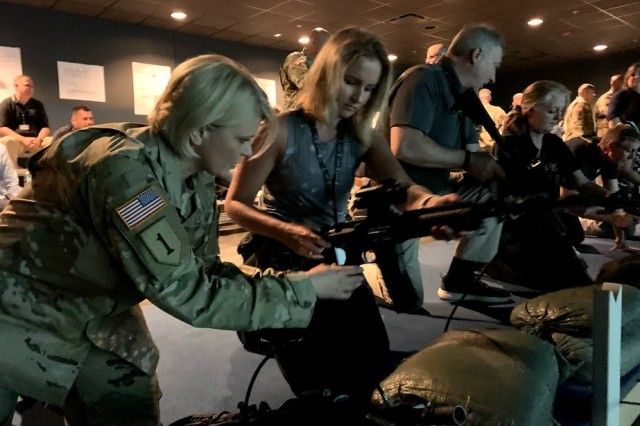 Col. Dina Wandler, brigade commander, U.S. Army 1st Recruiting Brigade, assists Melissa Friez, assistant superintendent of student support services, Pittsburgh Public Schools, with the M4 Rifle simulator while visiting the Engagement Skills Trainer on U.S. Army Recruiting Command's National Educator Tour at Fort Benning, Georgia, April 24.