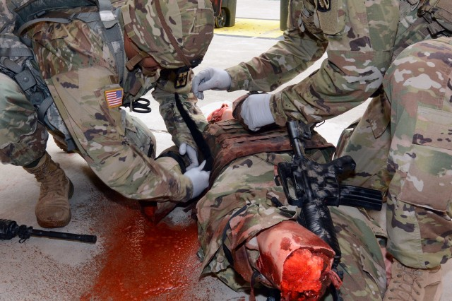 Soldiers attending Advanced Leaders Course at the AMEDDC&S HRCoE Noncommissioned Officer Academy practice treating a simulated leg amputation.