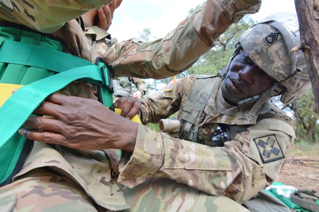 SSG Olayiwola Kugblenu, a 68P, M5 Nuclear Medicine Specialist with the 264th Medical Battalion, straps a simulated causality into a Kendrick Extraction Device (KED) while training at Camp Bullis, Tex.