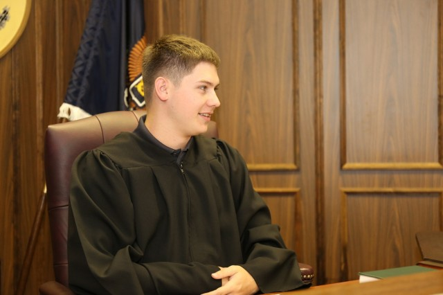 "Sean Canada, a senior at Zama American Middle High School, role-plays as the judge in a mock trial held April 26 in the U.S. Army Japan courtroom. Canada and 15 other ZAMHS seniors participated in the event as part of a ""Law Day"" celebration."