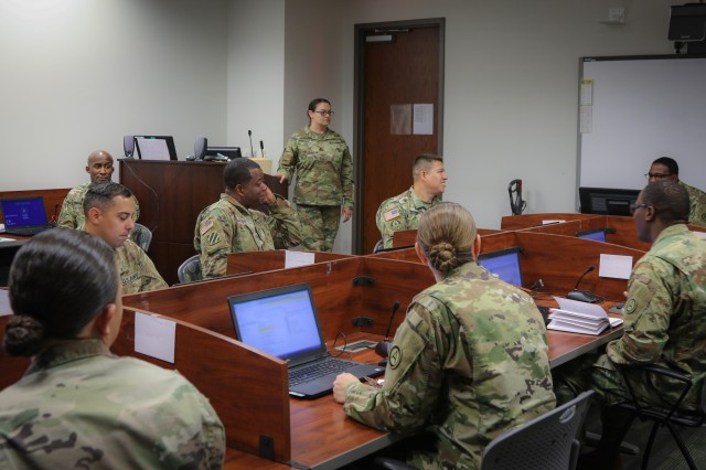Sgt. 1st Class Brooke Crytser (standing center), an assistant instructor for the U.S. Army Battle Staff Noncommissioned Officers Course and a personnel recovery intelligence NCO at U.S. Army Central, engages with students enrolled in the course at USARCENT headquarters on Shaw Air Force Base, S.C., July 27, 2018. BSNCOC provides technical and tactical curriculum relevant to the missions, duties and responsibilities assigned to battle staff members. (U.S. Army photo by Sgt. Von Marie Donato)