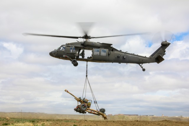 A UH-60 Black Hawk, piloted by members of the 4th Combat Aviation Brigade, 4th Infantry Division, picks up a M119 Howitzer during air assault training with Soldiers Bravo Battery, 2nd Battalion, 77th Field Artillery Regiment, 2nd Infantry Brigade Combat Team, 4th Inf. Div., at Fort Carson, Colorado, May 2, 2019. (U.S. Army photo by Staff Sgt. Neysa Canfield)