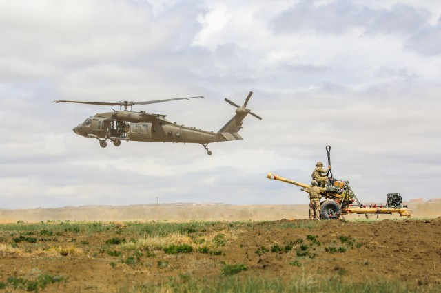 A UH-60 Black Hawk, piloted by members of the 4th Combat Aviation Brigade, 4th Infantry Division, hovers near a M119 Howitzer and Soldiers from Bravo Battery, 2nd Battalion, 77th Field Artillery Regiment, 2nd Infantry Brigade Combat Team, 4th Inf. Div., May 2, 2019, during air assault training on Fort Carson, Colorado. (U.S. Army photo by Staff Sgt. Neysa Canfield)