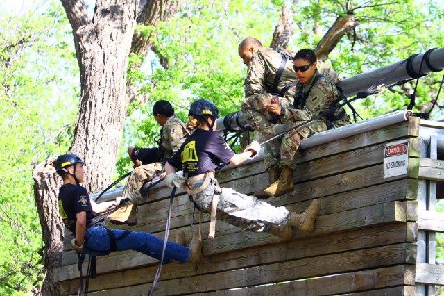 Drill Sergeant (Staff Sgt.) Michelle Solis (right), 1st Battalion, 19th Field Artillery, and other drill sergeants instruct JROTC cadets on rappelling down a 10-foot wall. After that, the cadets rappelled a 40-foot wall.