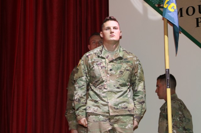 Spc. Jesse R. Wolfe, A Troop, 2nd Squadron, 1st Cavalry Regiment, 1st Stryker Brigade Combat Team, 4th Infantry Division, stands at attention as he is recognized for receiving the Distinguished Leader Award, at the Basic Leader Course graduation ceremony.