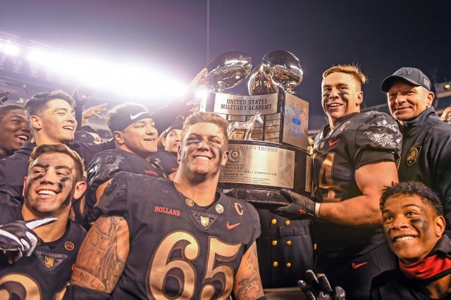 Army football players and head coach Jeff Monken pose with the Commander-in-Chief's Trophy after defeating Navy in Philadelphia, Pa., Dec. 8, 2018.