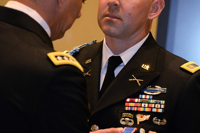 Gen. Stephen Townsend, commanding general of Training and Doctrine Command, pins Maj. Nicholas Eslinger, Command and General Staff Officer Course student, with the Distinguished Service Cross for Eslinger's actions while deployed as a second lieutenant to Iraq in October 2008 during a ceremony, May 3, at Fort Leavenworth, Kan. Eslinger was previously awarded the Silver Star for saving the lives of at least six Soldiers when he jumped on a grenade that had been thrown into an alley where his platoon was positioned, then he threw the grenade back toward the enemy after it did not go off. Townsend, who was present when Eslinger received the Silver Star, commented that Eslinger would have been presented the Medal of Honor posthumously if the grenade had gone off, and he requested to be the one to present Eslinger with the elevated medal.