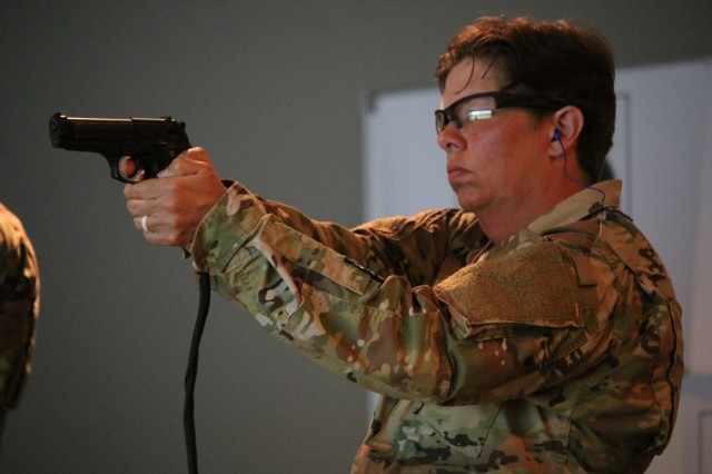 Staff Sgt. Tiffany Anderson shoots an M9 pistol at an indoor training facility at Fort Rucker, Alabama, as part of the AMCOM Best Warrior Competition. Anderson, who is stationed at Letterkenny Army Depot, Pennsylvania, was the winning non-commissioned officer and will compete at the Army Materiel Command competition in July.