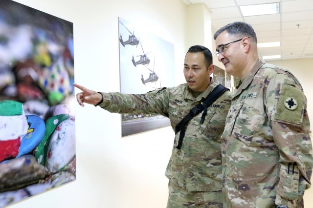 U.S. Army Sgt. Philip Ribas, 452d Combat Support Hospital, shows his imagery to Brig. Gen. Clint E. Walker, commanding general of 184th Sustainment Command, at Camp Arifjan, Kuwait, May 5, 2019. (U.S. Army National Guard photo by Sgt. Connie Jones)
