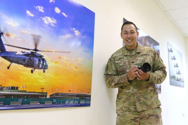 U.S. Army Sgt. Philip Ribas, 452d Combat Support Hospital, stands beside his imagery at Camp Arifjan, Kuwait, May 5, 2019. (U.S. Army National Guard photo by Sgt. Connie Jones)