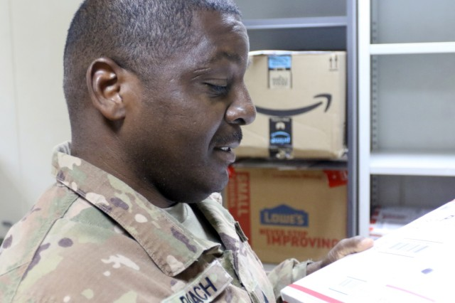 Sgt. Curtis Roach, 184th Sustainment Command, looks at a package at Camp Arifjan, Kuwait, April 29, 2019. (U.S. Army National Guard photo by Sgt. Connie Jones)