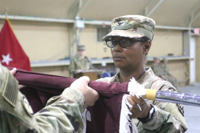 Col. Betty Demus, 349th Combat Support Hospital commander, uncases the unit's colors during a transfer of authority ceremony for United States Military Hospital-Kuwait at Camp Arifjan, Kuwait, May 6, 2019. (U.S. Army National Guard photo by Sgt. Connie Jones)