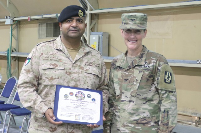 Kuwait Col. Raed Altajalli, assistant director of Kuwait North Military Medical Complex, and U.S. Army Col. Ellen Shannon-Ball, 452d Combat Support Hospital commander, stand together after he receives an award at Camp Arifjan, Kuwait, May 6, 2019. (U.S. Army National Guard photo by Sgt. Connie Jones)