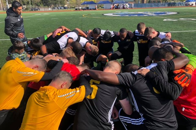 "The Army team huddles and kneels in prayer after winning the 2019 Armed Forces Men's Soccer Championship match at Naval Station Everett, Wash. April 20, 2019. The Army team came together ""Eleven as One"" to beat the Air Force 2-1."