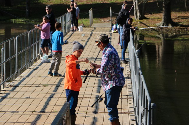 A volunteer helps during the fishing tournament at Red River Army Depot's Elliott Lake. The depot hosted the Youth Triathlon in support of two local group homes.