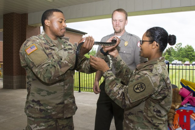 While handling a black kingsnake, Soldiers receive a water safety briefing from an Army Corps of Engineers representative during the 2019 Fort Knox Health and Safety Fair May 9, 2019, sponsored by U.S. Army Human Resources Command.