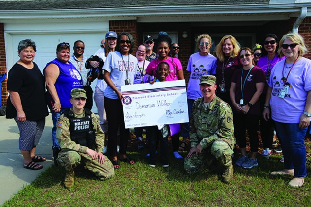 The Diamond Elementary Prize Patrol poses with Demarcus Walker, May 7, when the school and garrison representatives from Fort Stewart visited his house to help honor him and other children, during Month of the Military Child.