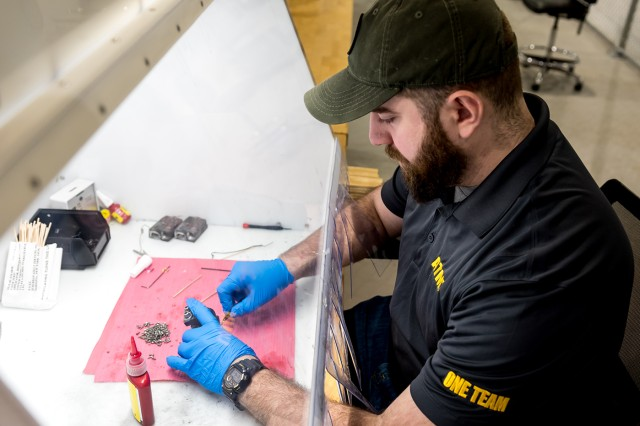 Electronics Mechanic Helper Brennen La Pere, applies a substance that will protect Individual Weapon System hardware from excess wear and tear.