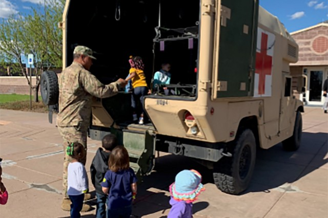 Spc. Fesuiaiga Lainia, a chemical, biological, radiological and nuclear specialist assigned to Bravo Troop, 3rd Squadron, 61st Cavalry Regiment, 2nd Infantry Brigade Combat Team, 4th Infantry Division, helps children enter the back of a High-Mobility Multipurpose Wheeled Vehicle Ambulance, April 24, 2019, during a static display at West Child Development Center on Fort Carson, Colorado. (U.S. Army photo by 1st Lt. Zachary Scott-Grunwald)