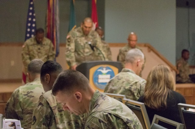 Chaplain (Capt.) Jose Rondon leads the prayer for the community while Soldiers bow their heads in silence.