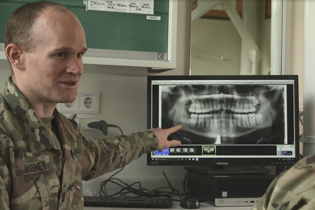Capt. Michael Mooney talks with a patient during a recent visit at the Grafenwoehr Dental Clinic. Mooney, a comprehensive dentist, started his Army career as an enlisted Soldier. It was after a bad dental experience, that he decided he wanted to make sure other Soldiers didn't have the same experience.