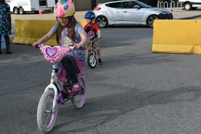 Children ride their bikes at the Fort Knox main Exchange where Fort Knox Bicycle Safety Day was held in the parking lot May 8. The event was designed to teach children how to safely ride their bicycles along Fort Knox streets and other roadways
