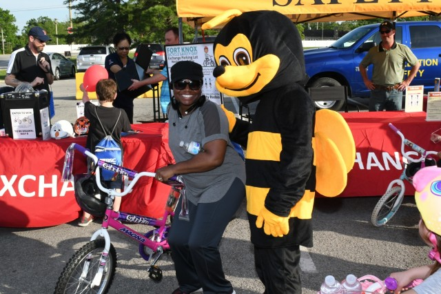 "Keyla Brown stands beside ""Bee Safety Bee"" and proudly displays the bicycle she won from the Bicycle Safety Day Drawing. Each bicycle came with a bicycle safety helmet."