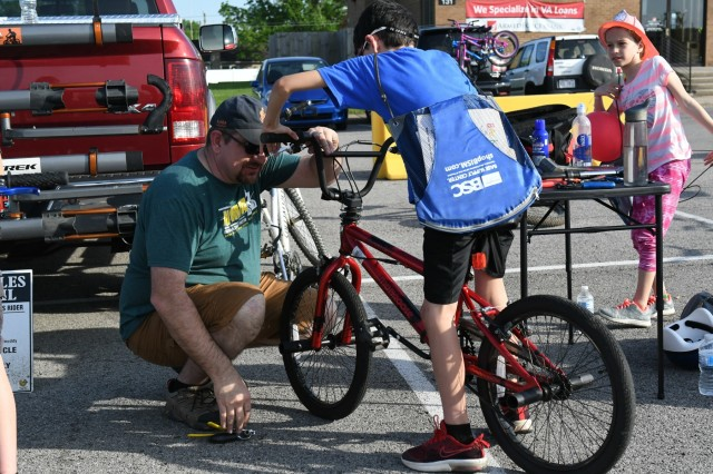 Lucas Bushen, age 10, holds his bicycle while Vince Carmen works to tighten his brakes before Lucas rides in the Bicycle Safety Rodeo. The rodeo was designed totest children's knowledge of bicycle hand-and-arm signals.