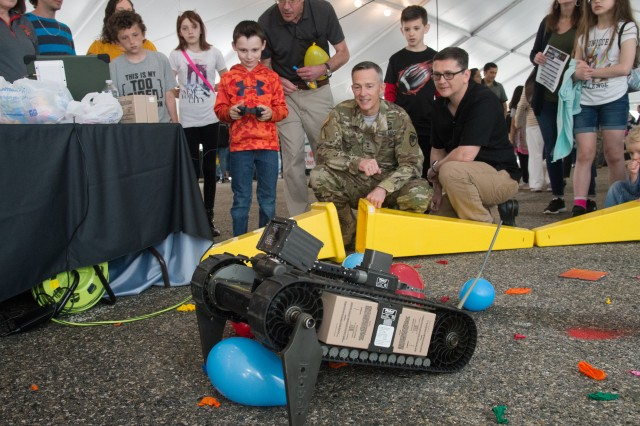 Aberdeen Proving Ground Senior Commander, Maj. Gen. Randy Taylor and his husband Lucas look on as a budding engineer prepares to burst a balloon using a remote-controlled robot. The action took place during the APG Discovery Fest 2019, May 4.