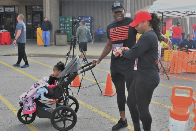 Capt. Melvin Obodoako and his wife, Morgan check their run times following the 14th Annual Run for the Red 5K while daughter, McKinley observes the other runners receiving their medals. May is Trauma Awareness Month and the Run for the Red event helps to raise awareness of the critical need for blood donations.