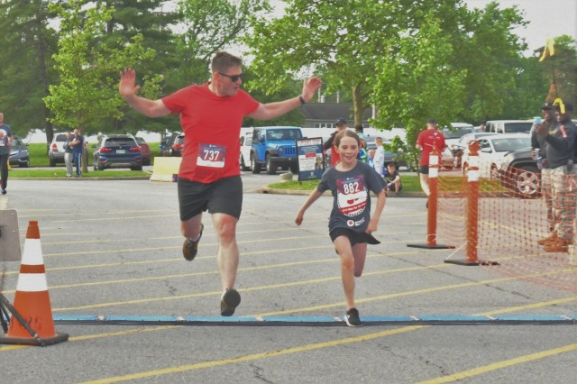Halyn Kramer finishes the 14th Annual Run for the Red 5K in front of her father, Maj. Stephen Kramer who cheers her accomplishment. Nearly 1,000 runners and walkers participated in the 14th Annual Run for the Red 5K/10K in support of the Fort Knox chapter of the American Red Cross at Fort Knox's main Exchange May 11.