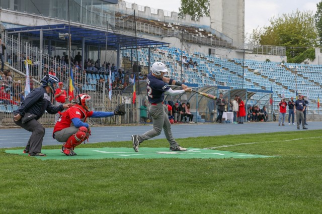 U.S. Army Soldier, Spc. Tommy Kennedy, 1442nd Firefighters, stationed at Mihail Kogalniceanu Air Base, Romania, batter for the U.S. Army volunteer baseball team, hits a single during the the third annual Jackie Robinson Trophy baseball game between U.S. Army Soldiers and the Romanian National Baseball Team at Farul Stadium, Constanta, May 11, 2019. U.S. Army Soldiers volunteered to participate in this friendly game of baseball to build cohesion with the Romanian community. (U.S. Army photo by Pfc. Andrew Wash)